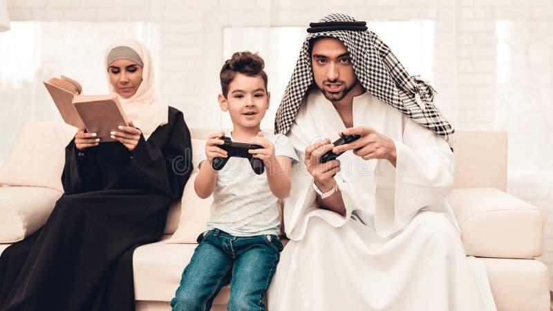 Família árabe feliz que joga no console em casa fotos de stock royalty free