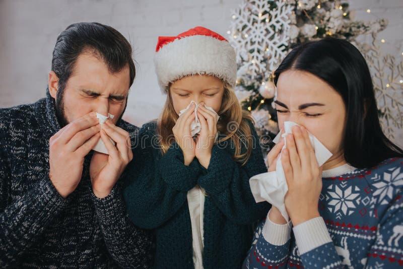 A família é doente no Natal que têm o lenço Os povos doentes têm o nariz ralo Christamas alegre e ano novo feliz foto de stock royalty free