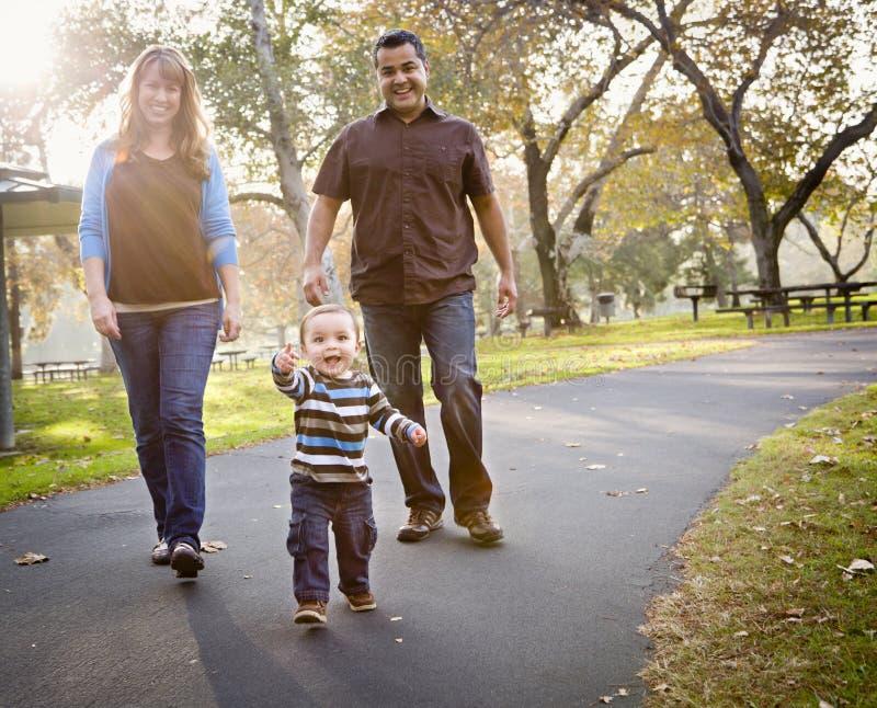 Família étnica feliz da raça misturada que anda no parque