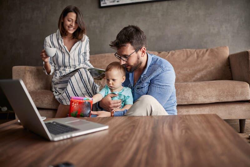 Família - acople passar o tempo feliz em casa com seu filho do bebê foto de stock