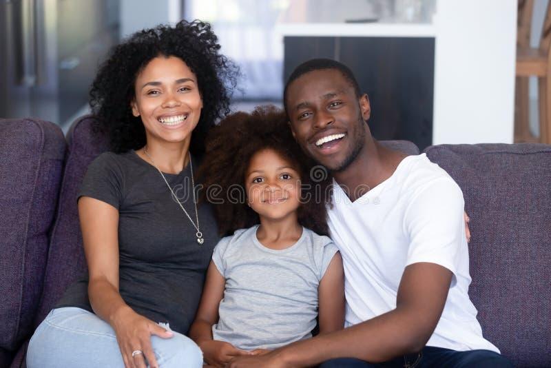 Família africana e filha que sentam-se no sofá que levanta para a câmera imagens de stock
