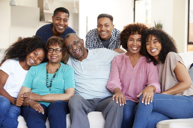 Família afro-americano da multi geração que senta em casa o sorriso à câmera fotos de stock
