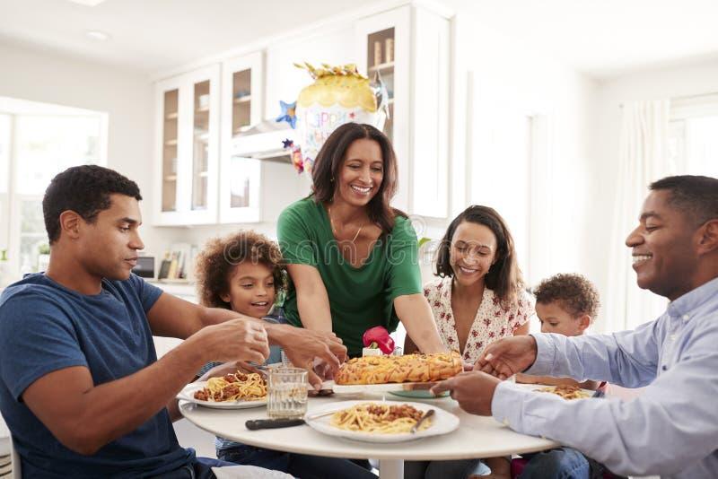 Família afro-americano de três gerações que senta-se junto na mesa de cozinha, com a avó que serve o alimento, fim acima fotos de stock