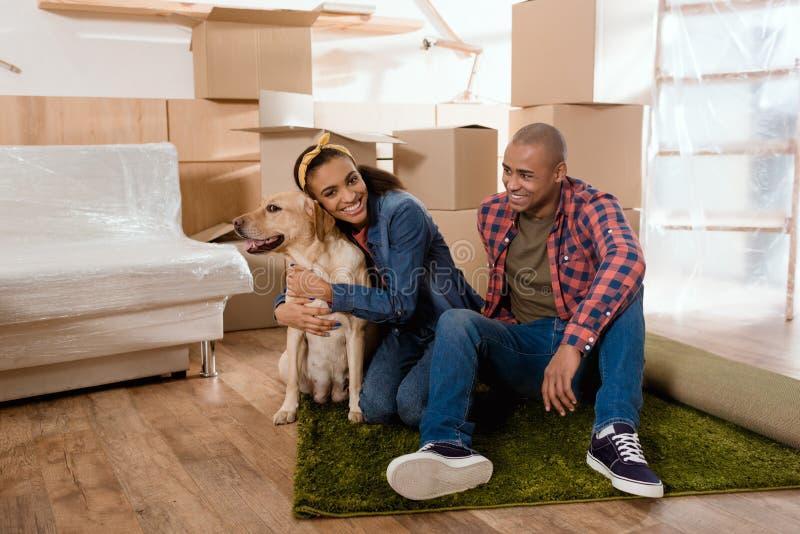 família afro-americano feliz nova com o cão de Labrador que move-se para imagens de stock