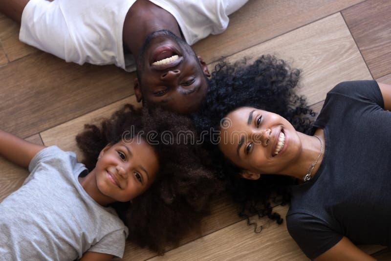 Família afro-americano feliz que encontra-se no assoalho que olha a câmera fotografia de stock
