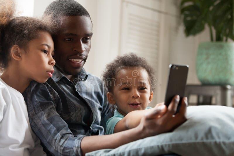 Família afro-americano feliz que usa o telefone celular junto fotografia de stock royalty free