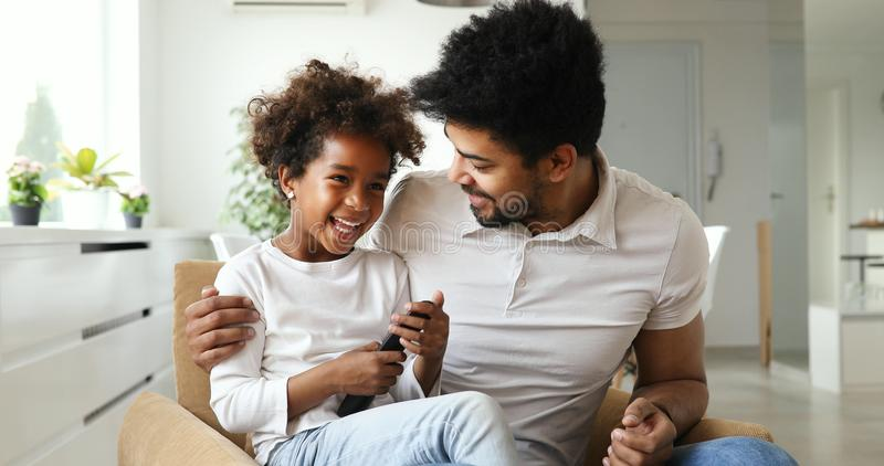 Família afro-americano relaxado que olha a tevê foto de stock