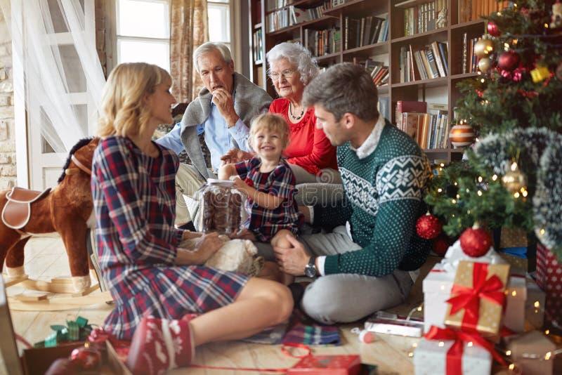 A família alegre comemora um feriado do Natal e comer cookies do mas x imagens de stock royalty free