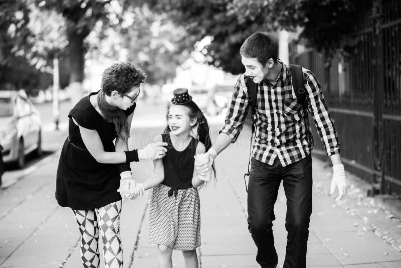 A família alegre de mimica guardando as mãos que anda abaixo da rua foto de stock royalty free