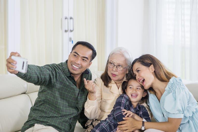 A família alegre de três gerações toma o selfie em casa fotos de stock royalty free