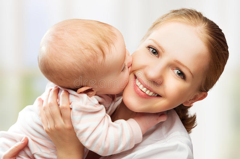 Família alegre feliz. Beijo da mãe e do bebê imagem de stock royalty free