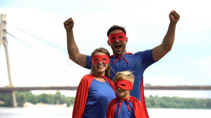 Família alegre nos trajes do superman que têm o divertimento, enganando ao redor, tempo de lazer foto de stock
