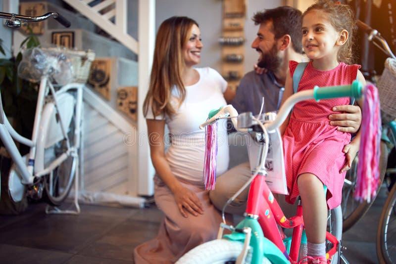 Fam?lia alegre que compra a bicicleta nova para a menina na loja da bicicleta imagem de stock