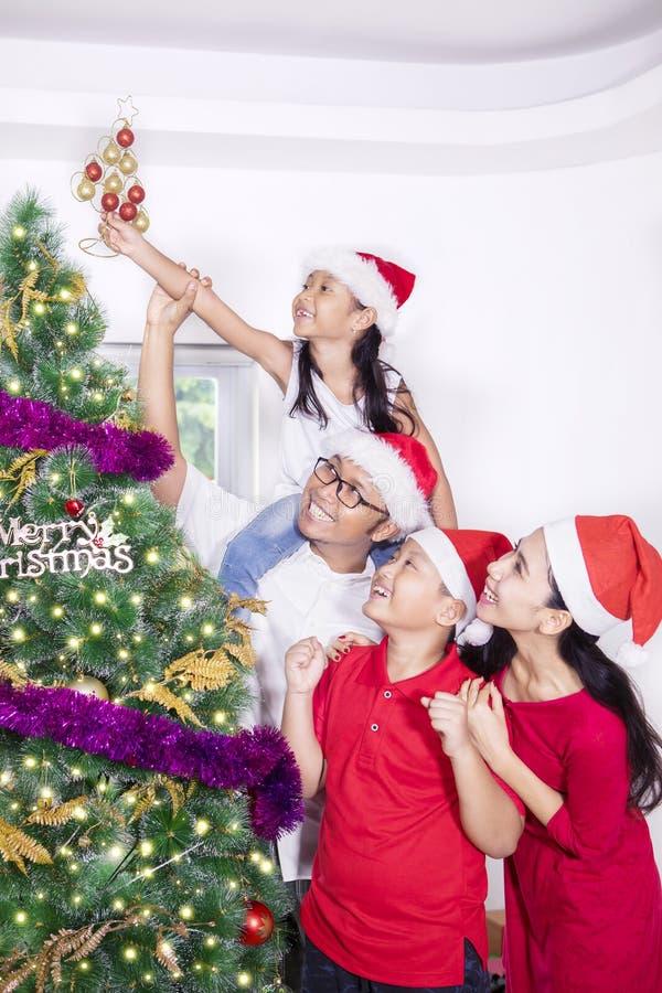 Família alegre que decora a árvore de Natal fotografia de stock