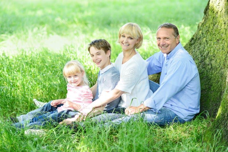 Família alegre que descansa sob a árvore imagem de stock royalty free