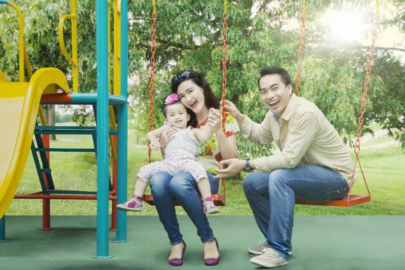Família alegre que joga junto no campo de jogos foto de stock