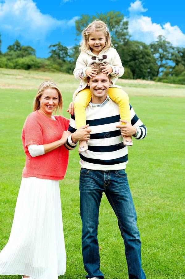 Família alegre que levanta de encontro ao fundo da natureza fotografia de stock