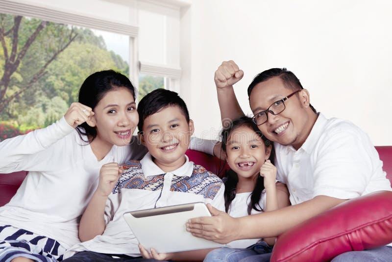 Família alegre que usa uma tabuleta digital no sofá fotos de stock