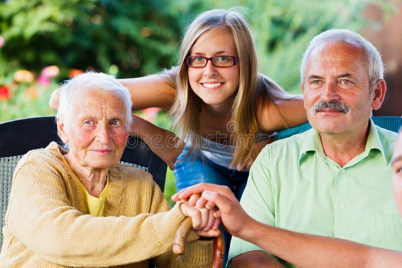 Família amável que visita a senhora idosa foto de stock