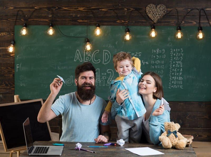 Família americana na mesa com jogo do filho com planos de papel Caçoe com pais na sala de aula com bandeira dos EUA, quadro sobre imagem de stock royalty free