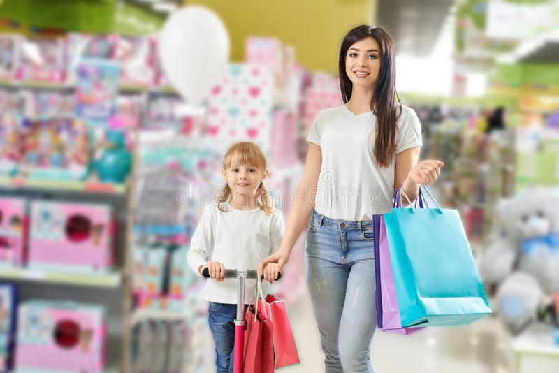 Família amigável que olha a câmera ao comprar brinquedos na loja fotos de stock royalty free