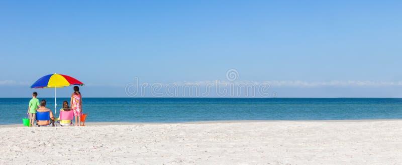 Família apenas na praia com guarda-chuva fotografia de stock