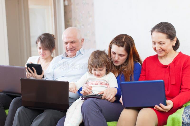 A família aprecia com poucos portáteis em casa imagens de stock