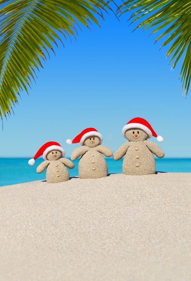 Família arenosa dos bonecos de neve do Natal em chapéus de Santa em Palm Beach fotos de stock royalty free
