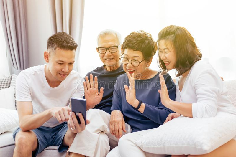 Família asiática com crianças adultas e os pais superiores que fazem uma chamada video e que acenam no chamador em casa imagens de stock royalty free