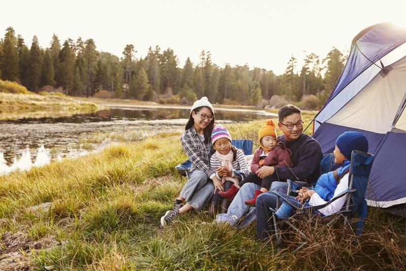 A família asiática em uma viagem de acampamento relaxa fora de sua barraca imagem de stock