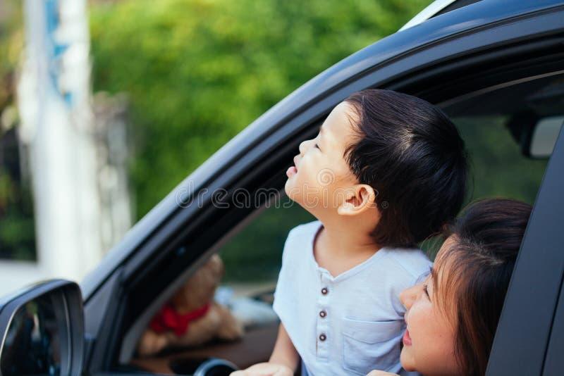 A família asiática feliz está olhando acima no céu e está viajando na viagem por estrada, indo para uma movimentação para férias fotografia de stock