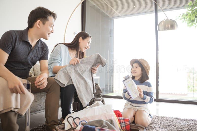 A família asiática feliz está preparando-se para o curso em casa A filha e o pai da mamã estão embalando malas de viagem para a v imagens de stock