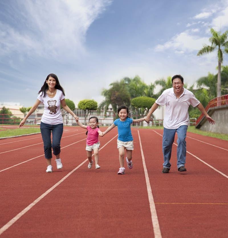 Família asiática feliz que funciona junto
