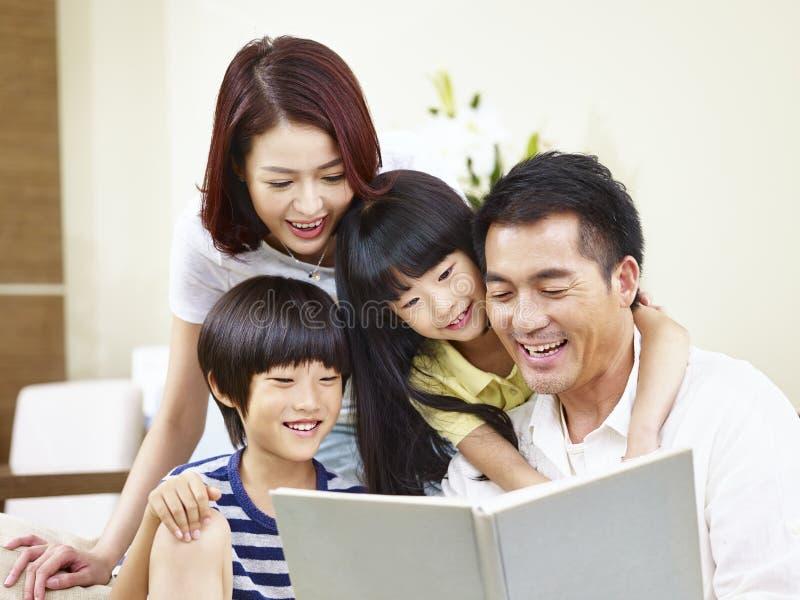 Família asiática feliz que lê um livro em casa fotografia de stock