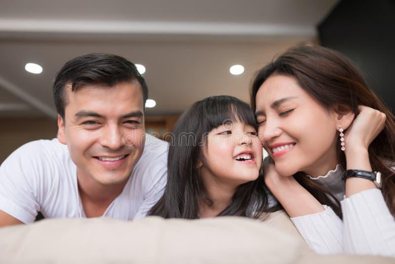 Família asiática feliz que passa o tempo junto no sofá na sala de visitas Fam?lia e conceito home fotografia de stock