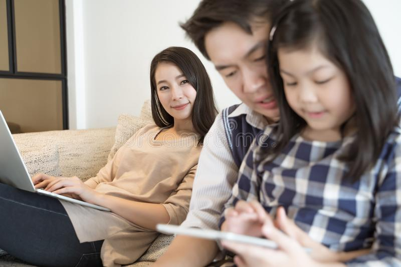 Família asiática feliz que passa o tempo junto no sofá na sala de visitas Fam?lia e conceito home foto de stock royalty free