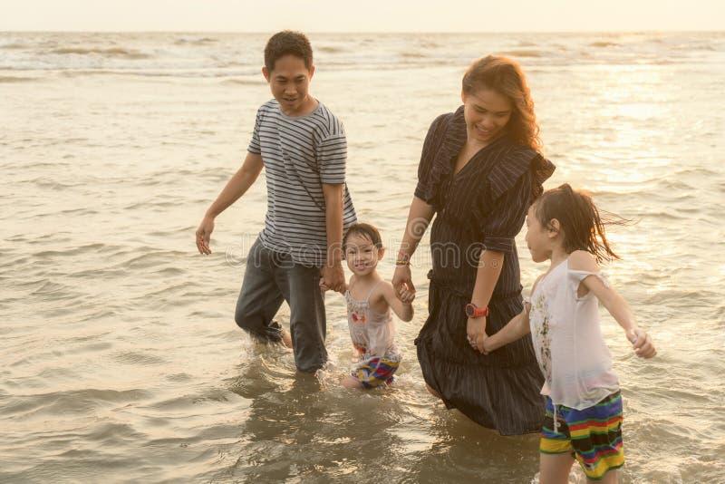 Família asiática feliz que tem o divertimento na praia no por do sol fotografia de stock royalty free
