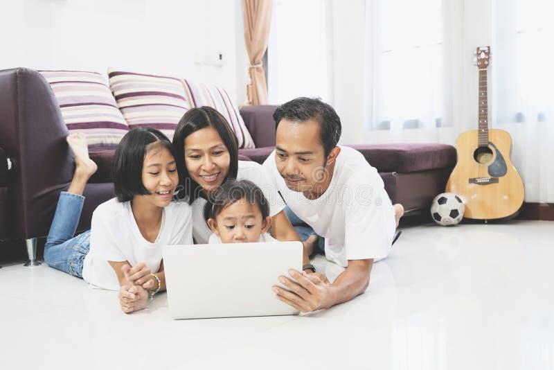 Família asiática feliz que usa um laptop imagens de stock