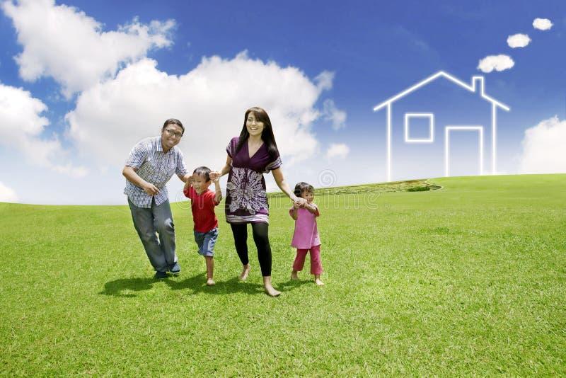 Família asiática nova com uma casa desenhada no campo fotografia de stock