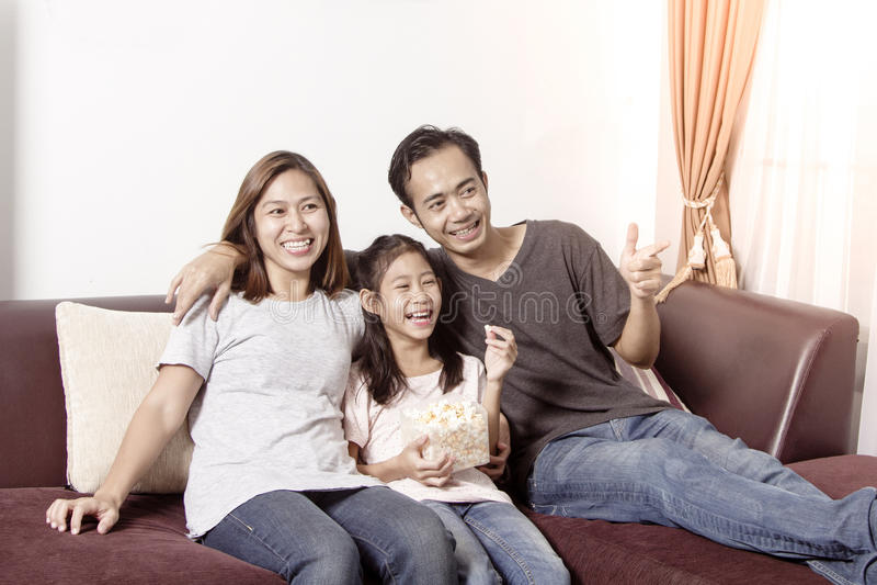Família asiática nova que olha a tevê junto em casa imagens de stock