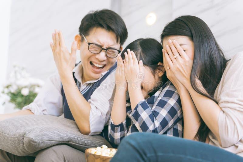 Família asiática que olha filmes assustadores em casa imagens de stock royalty free