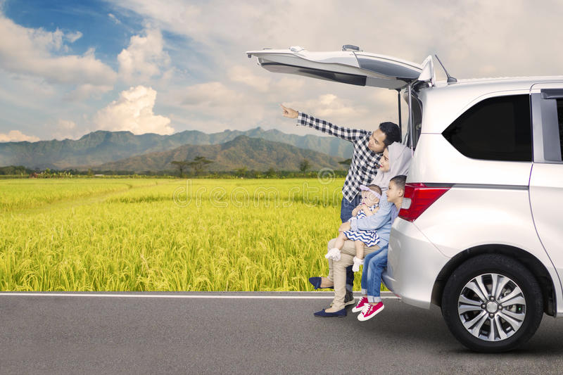 Família asiática que senta-se atrás de um carro fotografia de stock royalty free