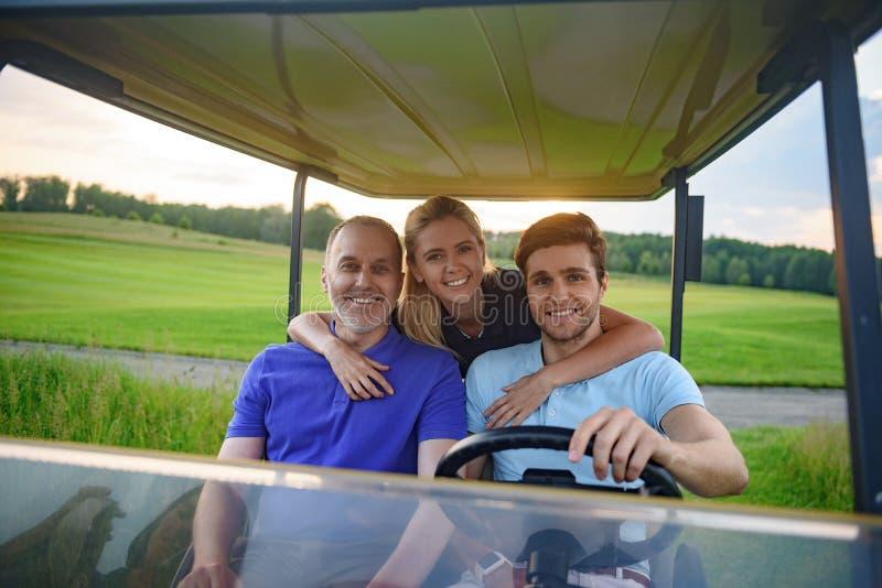 Família atrativa em seu carrinho de golfe imagens de stock royalty free
