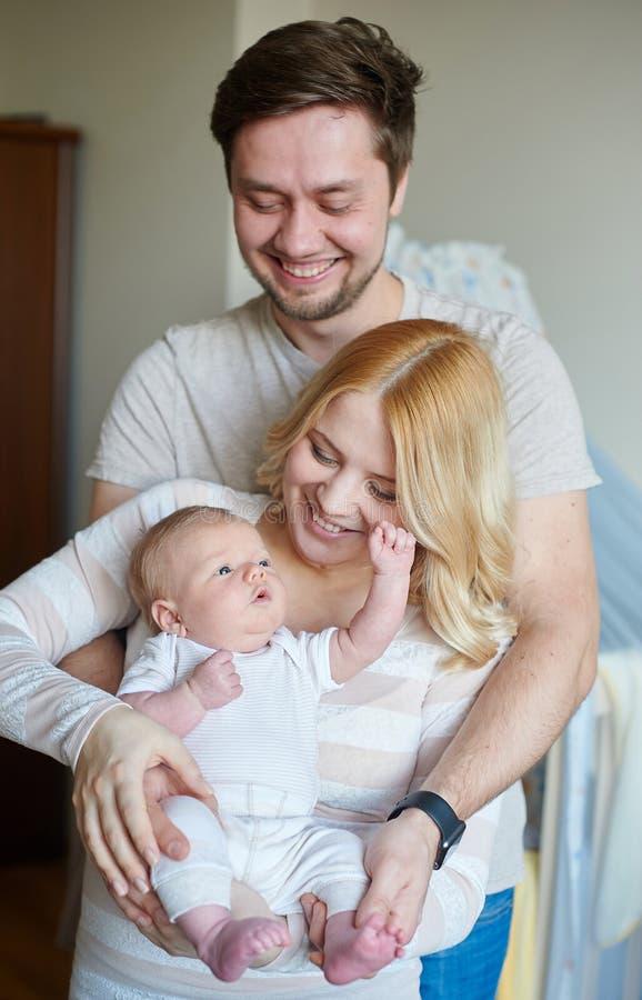 A família atrativa nova feliz parents com bebê recém-nascido imagem de stock