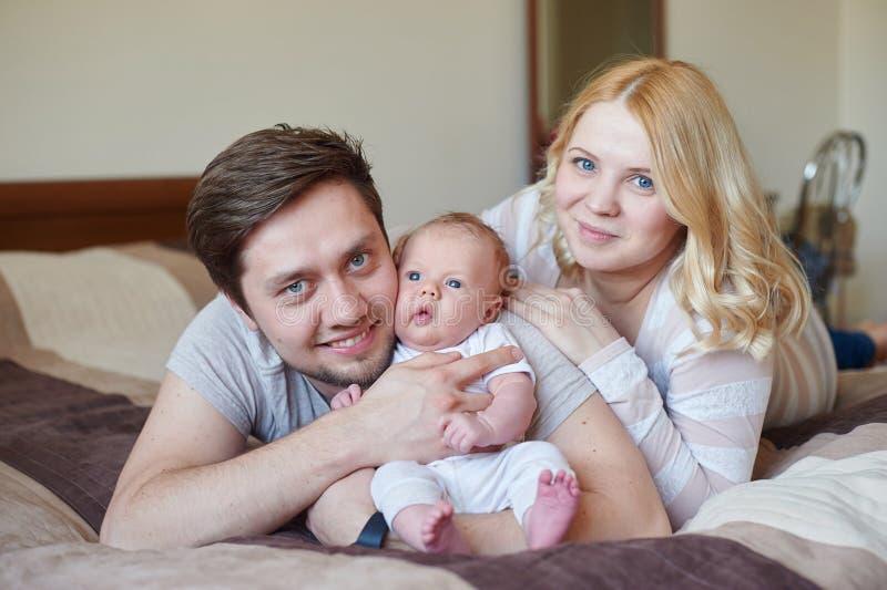 A família atrativa nova feliz parents com bebê recém-nascido fotografia de stock royalty free