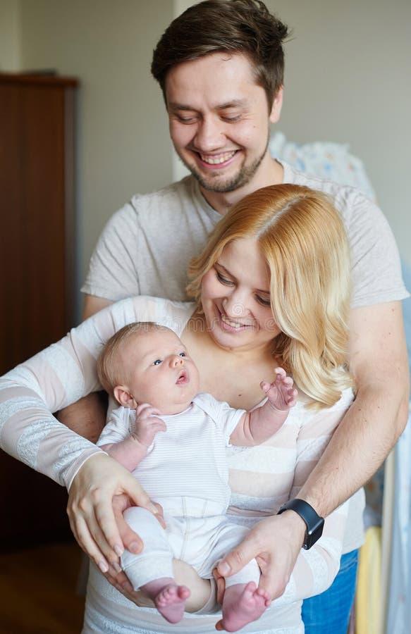 A família atrativa nova feliz parents com bebê recém-nascido fotografia de stock