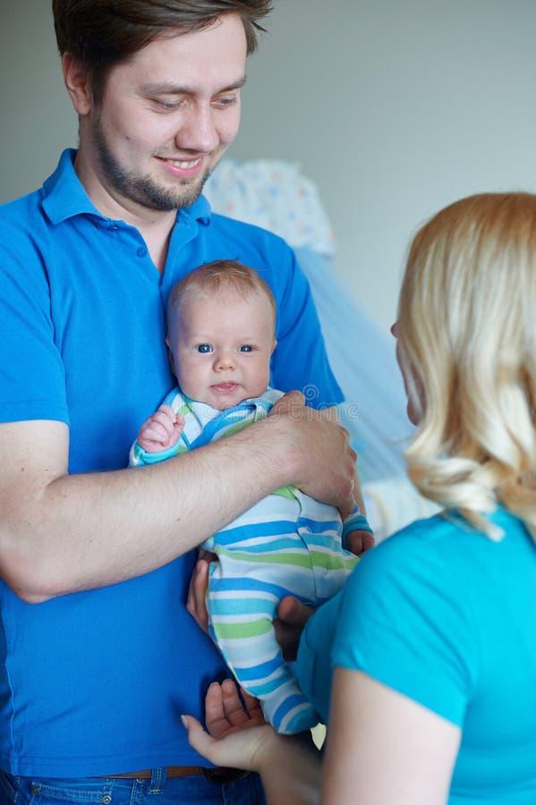 A família atrativa nova feliz parents com bebê recém-nascido foto de stock