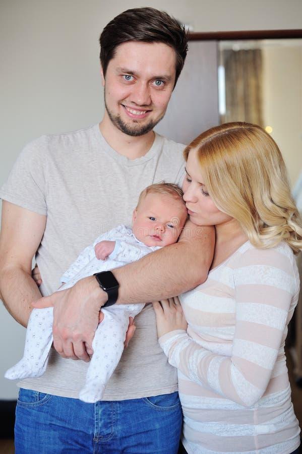 A família atrativa nova feliz parents com bebê recém-nascido imagem de stock royalty free