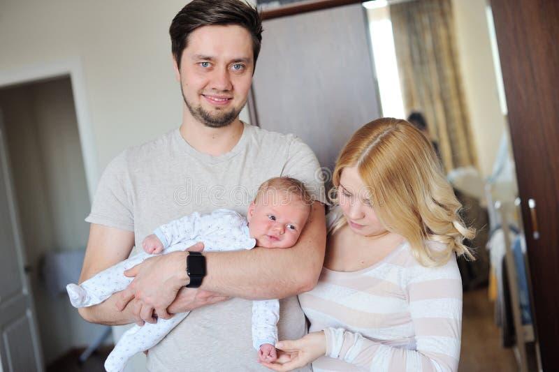 A família atrativa nova feliz parents com bebê recém-nascido imagens de stock