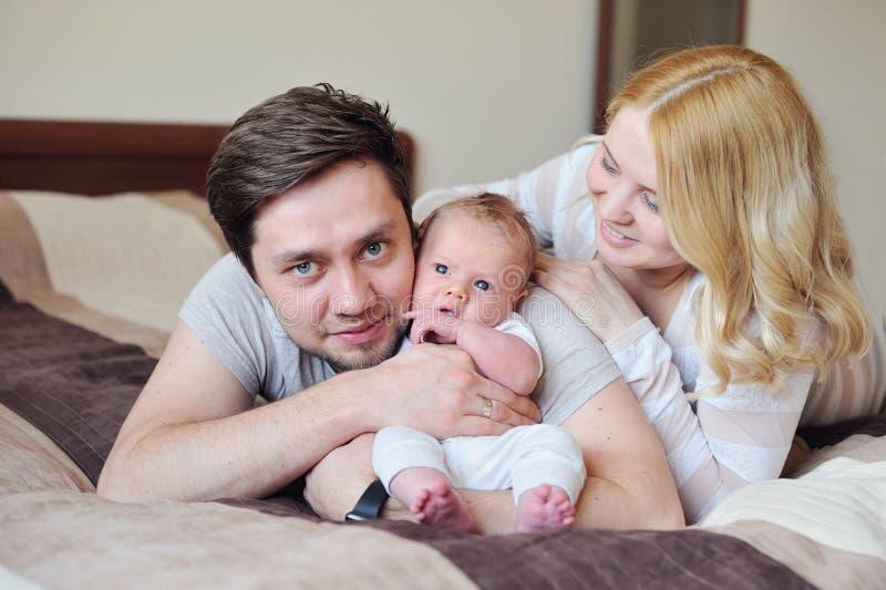 A família atrativa nova feliz parents com bebê recém-nascido imagens de stock royalty free